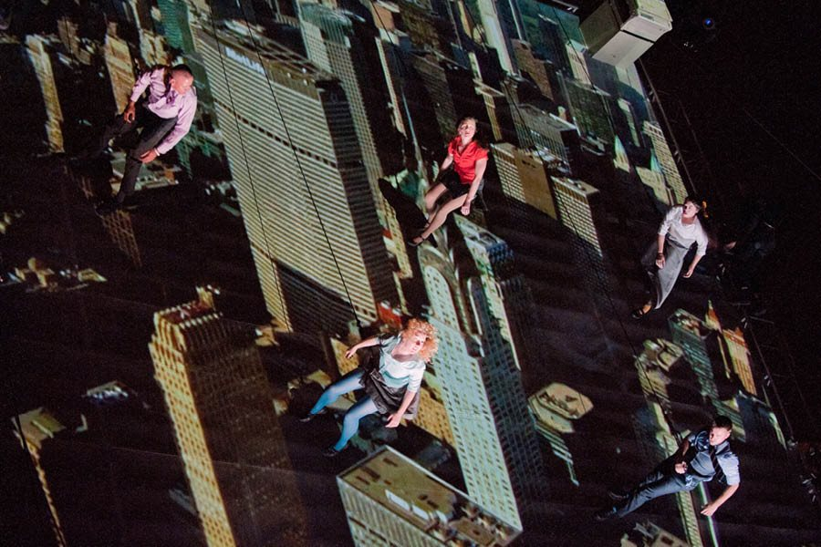 A group of people hanging from harness's from skyscraper reflections