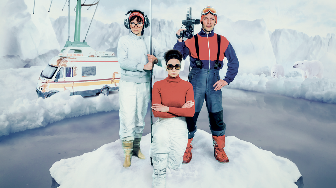 Three actors standing in the arctic with film gear