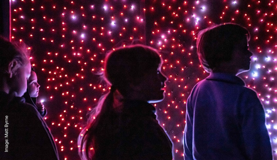 Silhouettes of children against pink speckled lights